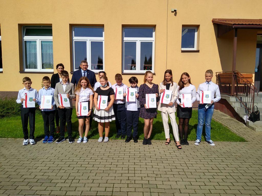 Uczniowie z Panem Burmistrzem i Panią Sekretarz przed budynkiem szkoły.