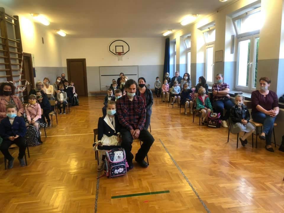 Uczniowie klasy pierwszej z rodzicami na sali gimnastycznej
