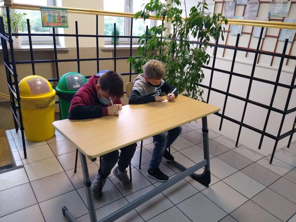 Uczennice klasy 4 w ławce szkolnej rozwiązuja zadania