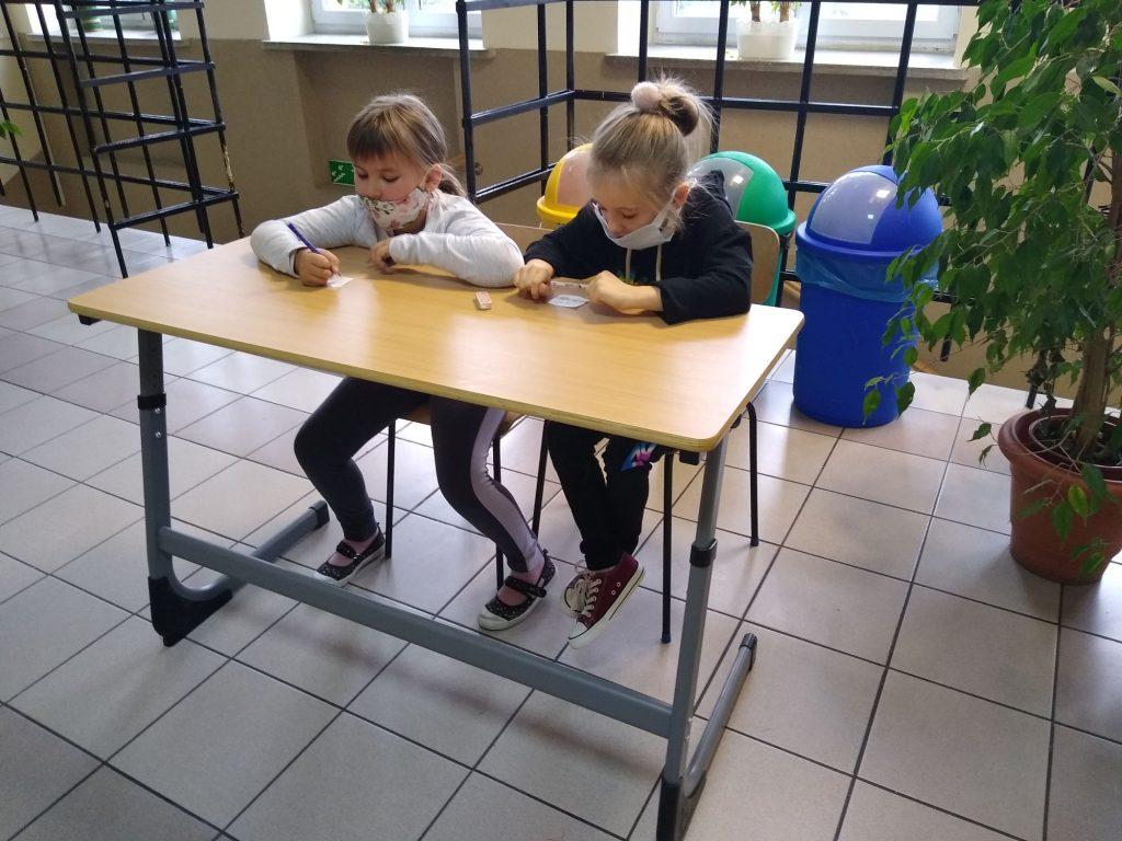 Uczennice klasy 3 w ławce szkolnej rozwiązuja zadania