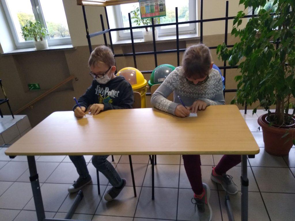 Uczniowie klasy 3 w ławce szkolne rozwiązuja zadania
