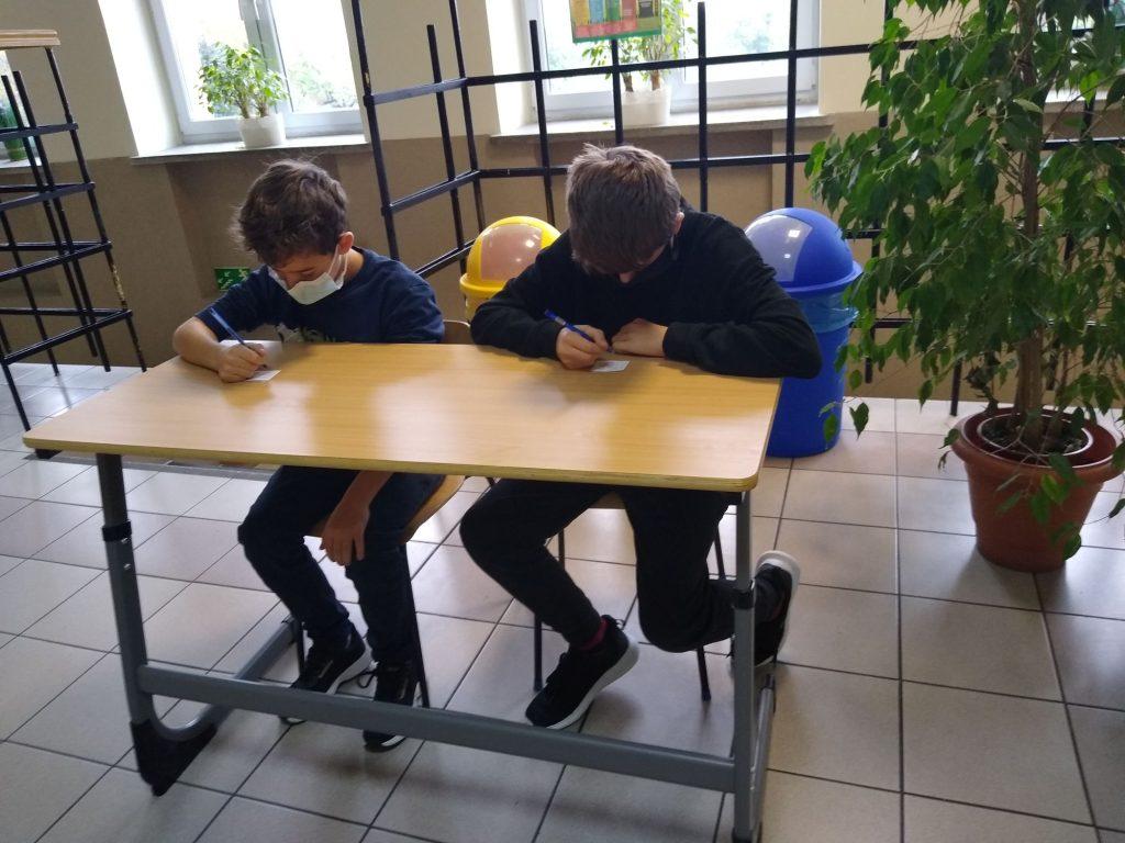 Uczniowie klasy 6 w ławce szkolnej rozwiązuja zadanie.