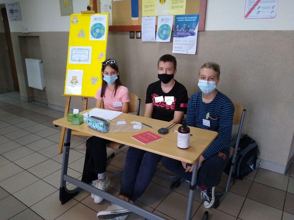 Uczniowie egzaminatorzy w ławce szkolnej.
