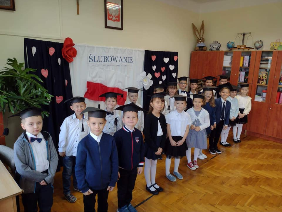Uczniowie klasy pierwszej w sali lekcyjnej w tle napis ŚLUBOWANIE